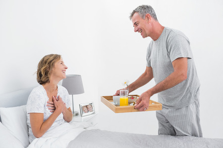 Loving husband bringing breakfast in bed to wife in bedroom at home photo