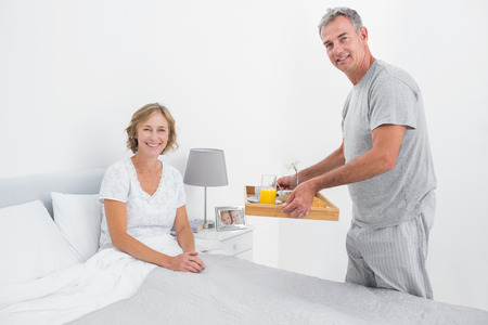 Happy husband bringing breakfast in bed to wife smiling at camera in bedroom at home photo