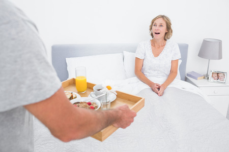 Husband bringing breakfast in bed to surprised wife in bedroom at home photo