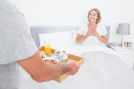 bed and breakfast: Husband bringing breakfast in bed to delighted wife in bedroom at home Stock Photo