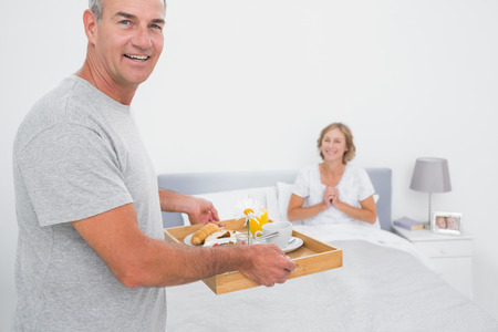 Happy husband bringing breakfast in bed to delighted wife looking at camera in bedroom at home photo