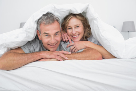 domiciles: Cheerful couple under the duvet smiling at camera in bedroom at home