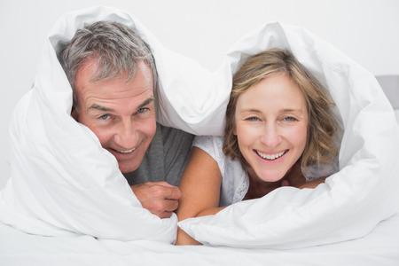 edred�n: Feliz pareja de mediana edad bajo el edred�n sonriendo a la c�mara en el dormitorio en casa