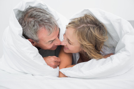 rubbing noses: Loving middle aged couple under the duvet rubbing noses in bedroom at home
