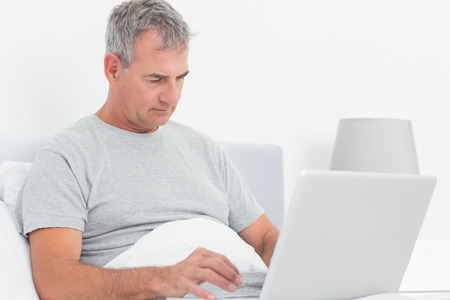grey haired: Grey haired man using his laptop in bed in bedroom at home