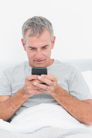 grey haired: Smiling grey haired man sending a text in bed in bedroom at home Stock Photo