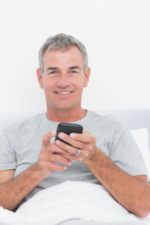 grey haired: Happy grey haired man sending a text in bed looking at camera in bedroom at home Stock Photo