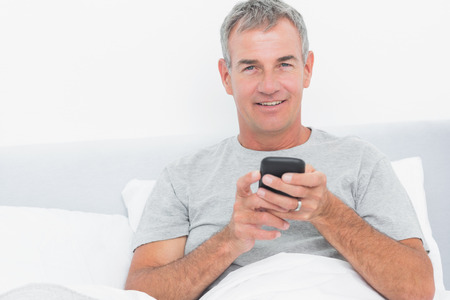 grey haired: Cheerful grey haired man sending a text in bed smiling at camera in bedroom at home