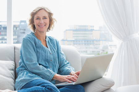 Content blonde woman sitting on her couch using laptop smiling at camera at home in the sitting room photo