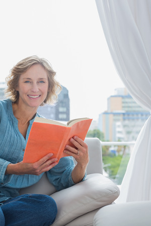 Happy blonde woman sitting on her couch holding a book smiling at camera at home in the sitting room photo