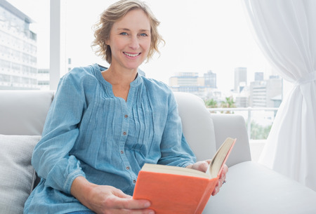 Content blonde woman sitting on her couch holding a book smiling at camera at home in the sitting room photo