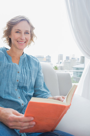 Blonde woman sitting on her couch reading a book smiling at camera at home in the sitting room photo