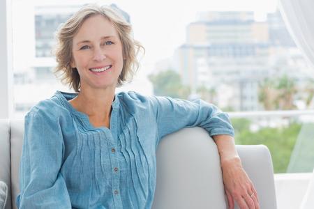 ��smiling: Mujer feliz que se relaja en el sof� en casa, en la sala de estar