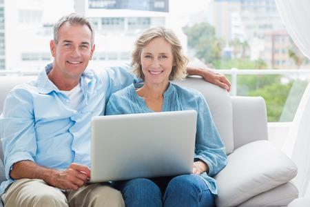 person computer: Gl�ckliches Paar entspannt auf der Couch mit dem Laptop l�chelnd in die Kamera zu Hause im Wohnzimmer