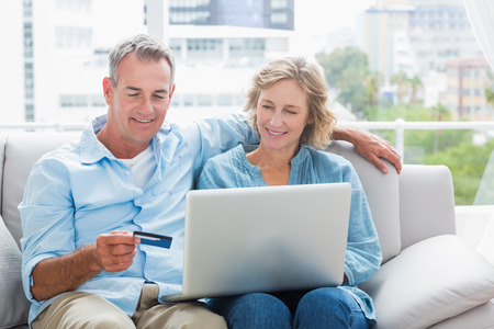 house shopping: Smiling couple sitting on their couch using the laptop to buy online at home in the sitting room