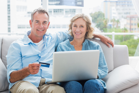 Happy couple sitting on their couch using the laptop to buy online smiling at camera at home in the sitting room photo