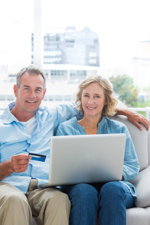 Cheerful couple sitting on their couch using the laptop to buy online looking at camera at home in the sitting room photo