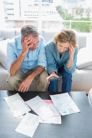 figuring: Worried couple sitting on their couch paying their bills at home in the living room Stock Photo