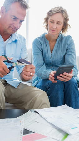 Wife watching her husband cut credit card in half at home in the living room Stock Photo - 25711998