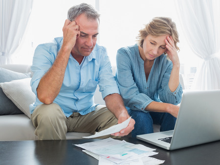 homely: Worried couple paying their bills online with laptop at home in the living room