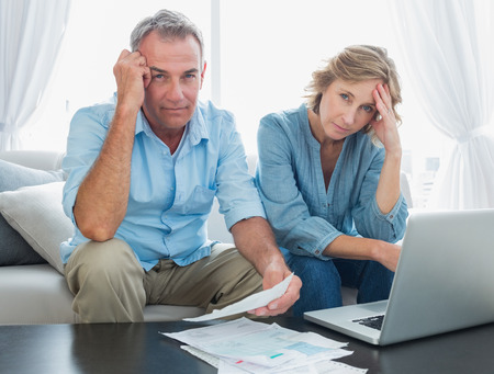 Anxious couple paying their bills online with laptop at home in the living room photo