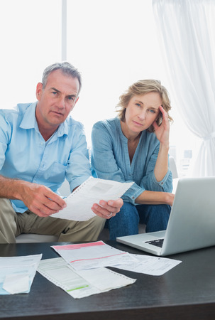 Anxious couple paying their bills online with laptop looking at camera at home in the living room photo