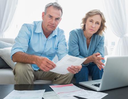 factura: Preocupados par el pago de sus facturas en línea con el ordenador portátil mirando a la cámara en casa, en la sala de estar Foto de archivo