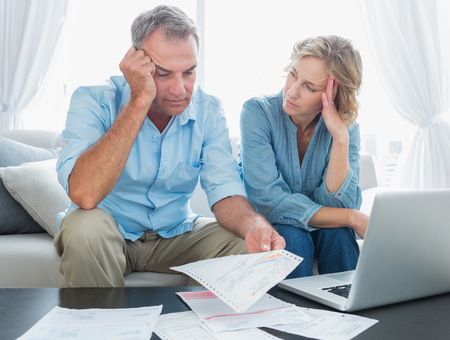 Worried couple using their laptop to pay their bills at home in the living room Stock Photo