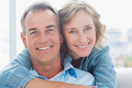自宅リビング ルームでソファの上に彼女の夫を後ろから抱き締める笑顔の女性 写真素材