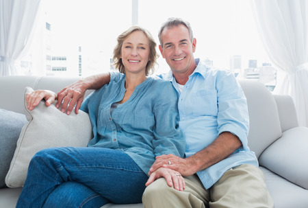 pareja en casa: Pareja de mediana edad que se relaja en el sofá sonriendo a la cámara en casa, en la sala de estar Foto de archivo