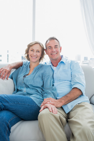Middle aged couple sitting on the couch smiling at camera at home in the living room Stock Photo