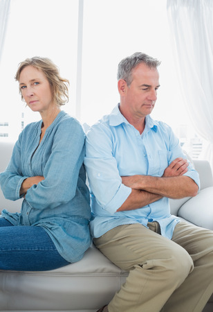 Middle aged couple sitting on the sofa not speaking after a fight with woman looking at camera at home in the living room photo