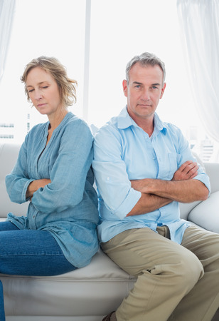 Middle aged couple sitting on the sofa not speaking after a dispute with man looking at camera at home in the living room photo