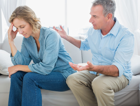 homely: Middle aged couple sitting on the couch having a dispute at home in the living room Stock Photo