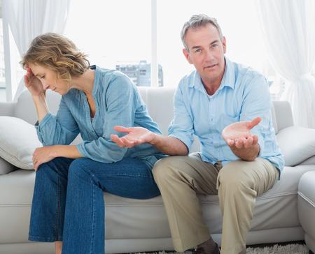 pareja discutiendo: Argumentando pareja de mediana edad sentados en el sofá con el hombre señalando a la cámara en casa, en la sala de estar Foto de archivo
