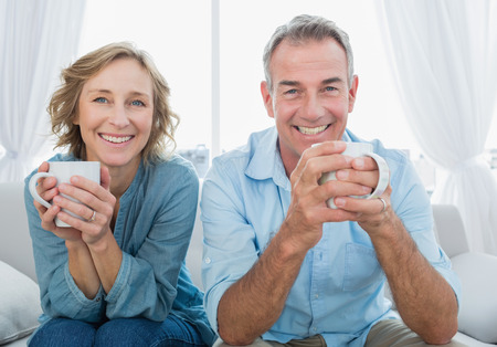 fair woman: Smiling middle aged couple sitting on the couch having coffee looking at camera at home in the living room Stock Photo