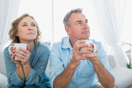 Thoughtful middle aged couple sitting on the couch having coffee looking away at home in the living room Imagens