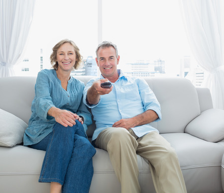 changing channel: Content middle aged couple sitting on the couch watching tv at home in the living room