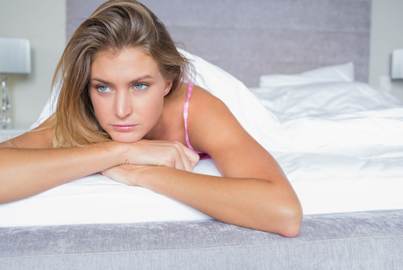 Thoughtful blonde lying on her bed in bedroom at home photo