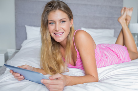 Happy blonde lying on her bed using her digital tablet smiling at camera in bedroom at home photo