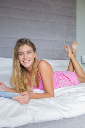 Happy blonde lying on bed using her digital tablet smiling at camera in bedroom at home photo