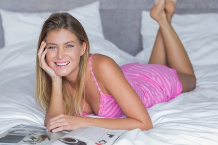 Beautiful blonde lying on her bed reading magazine smiling at camera at home in bedroom photo