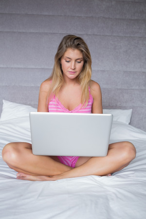 Smiling blonde woman sitting on her bed using laptop at home in bedroom photo