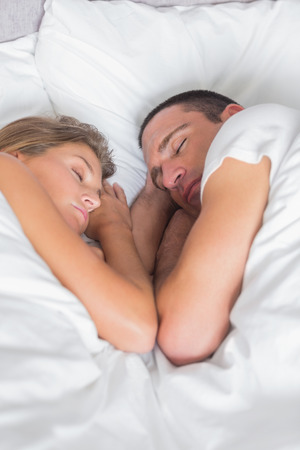 Cute couple asleep together in bed at home in bedroom photo