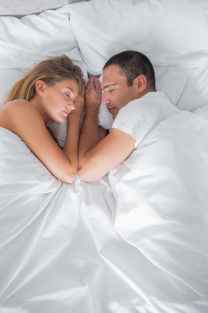 Cute couple lying asleep in bed overhead shot at home in bedroom photo
