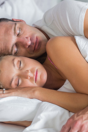Attractive couple sleeping and spooning in bed at home in bedroom photo