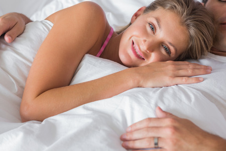 Smiling woman lying on husbands chest in bed looking at camera at home in bedroom photo