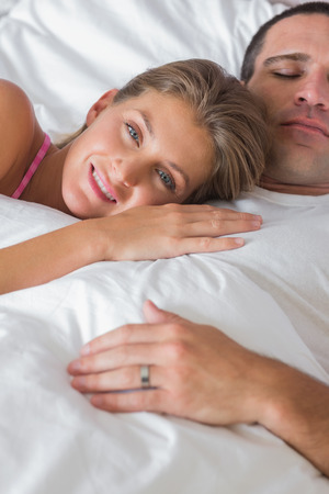 Happy woman lying on husbands chest in bed smiling at camera at home in bedroom photo