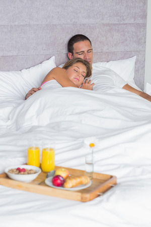 Couple asleep with breakfast tray on bed at home in bedroom photo