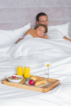 Attractive couple asleep with breakfast tray on bed at home in bedroom photo